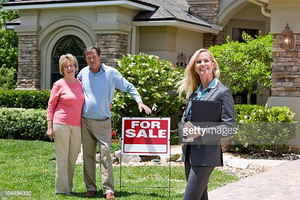 Real estate agent and senior couple by For Sale sign