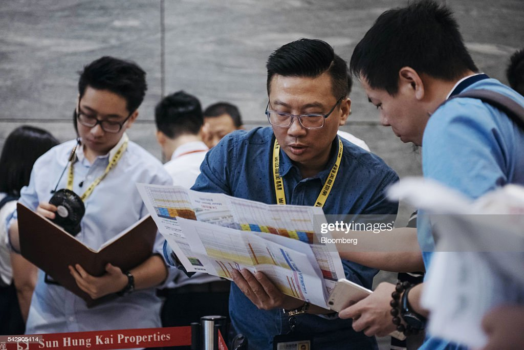 A real estate agent, center, shows a potential buyer, right, a pamphlet advertisement for Park Yoho Venezia, a residential property developed by Sun Hung Kai Properties Ltd., outside the property's sales office in Hong Kong, China, on Saturday, June 25, 2016. Sun Hung Kai, Hong Kong's largest developer by market value, is offering mortgages worth as much as 120 percent of a home's value at one of its projects as sales have slumped in the city. Photographer: Anthony Kwan/Bloomberg via Getty Images