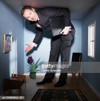 Real estate agent displaying small living room, smiling, portrait : Stock Photo