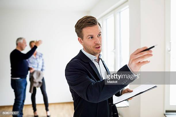 Real estate agent examining house with couple discussing in background