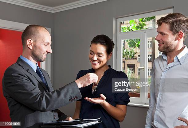 A real estate agent giving a couple the keys to their new home