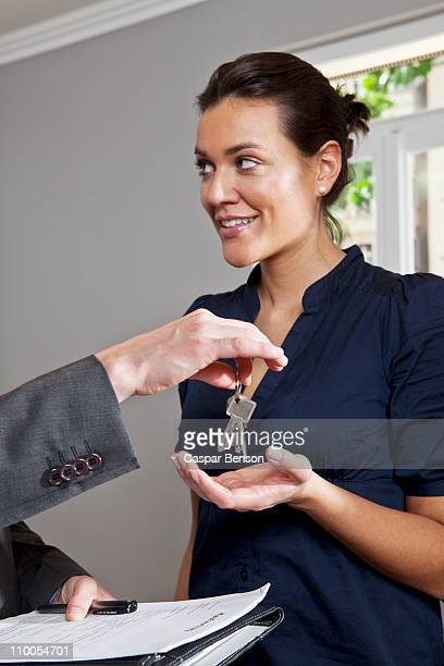 A real estate agent giving a woman the keys to her new home