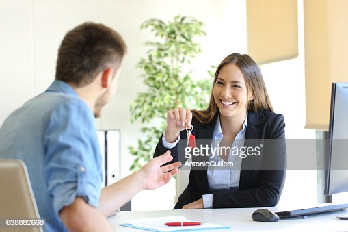 Real estate agent giving house keys to a customer : Stock Photo