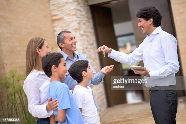 Real estate agent giving keys to a family