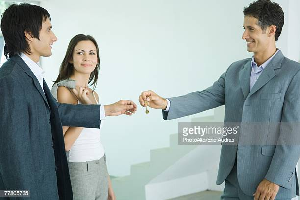 Real estate agent handing keys to young couple