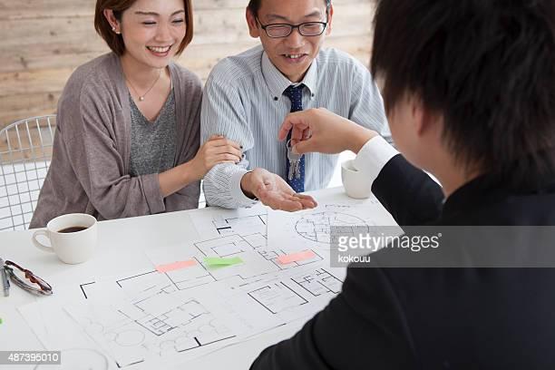 Real estate agent zukommende Wegstrecke Schlüssel zu Junges Paar