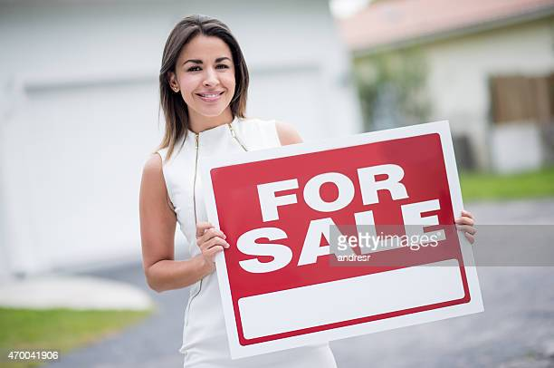 Real estate agent holding a FOR SALE sign