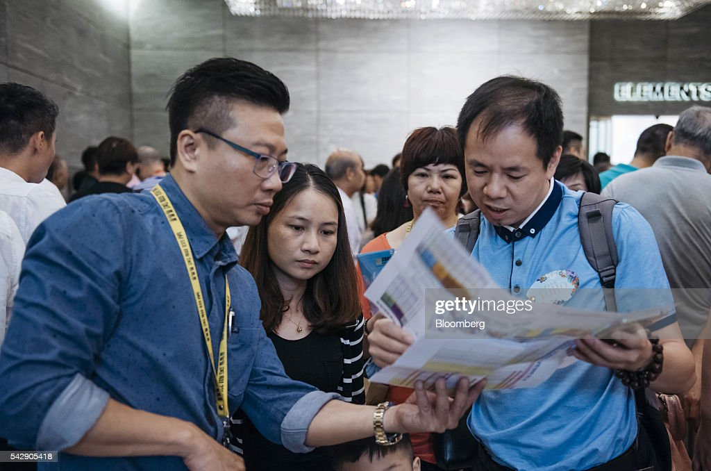 A real estate agent, left, shows potential buyers pamphlet advertisements for Park Yoho Venezia, a residential property developed by Sun Hung Kai Properties Ltd., outside the property's sales office in Hong Kong, China, on Saturday, June 25, 2016. Sun Hung Kai, Hong Kong's largest developer by market value, is offering mortgages worth as much as 120 percent of a home's value at one of its projects as sales have slumped in the city. Photographer: Anthony Kwan/Bloomberg via Getty Images