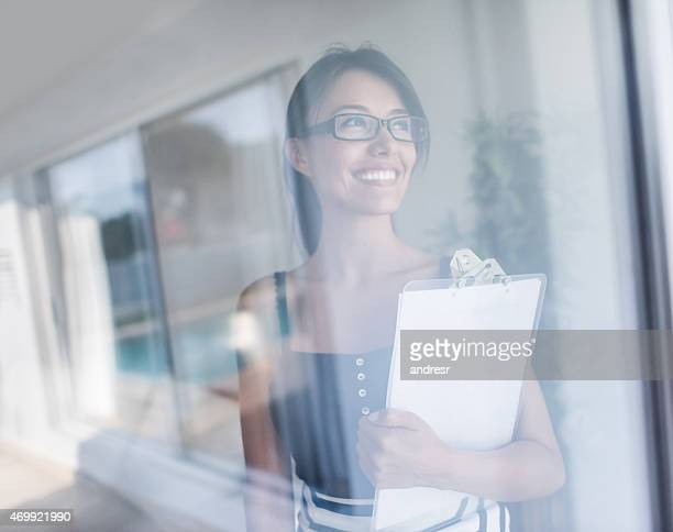 Real estate agent looking through window