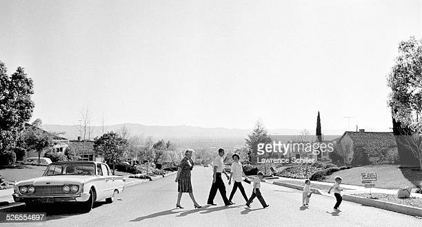 Real estate agent Mary Graham walks prospective homebuyers Ken and Carol Barnhart and their children across a suburban street to look at a home...