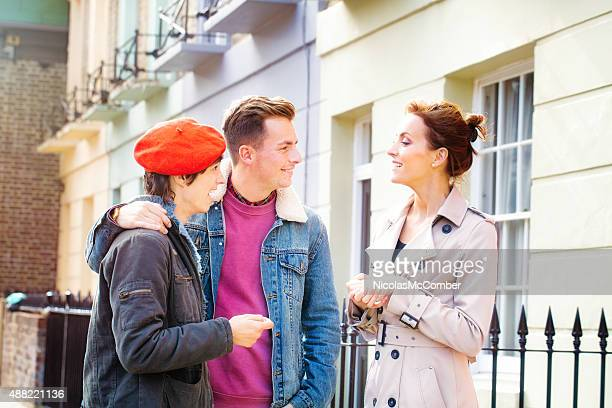 Real estate agent pitches excited young couple new home