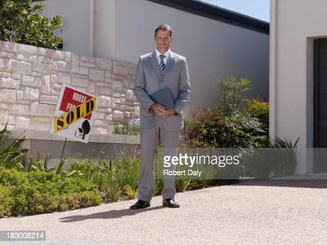 Real estate agent posing with sold home : Stock Photo
