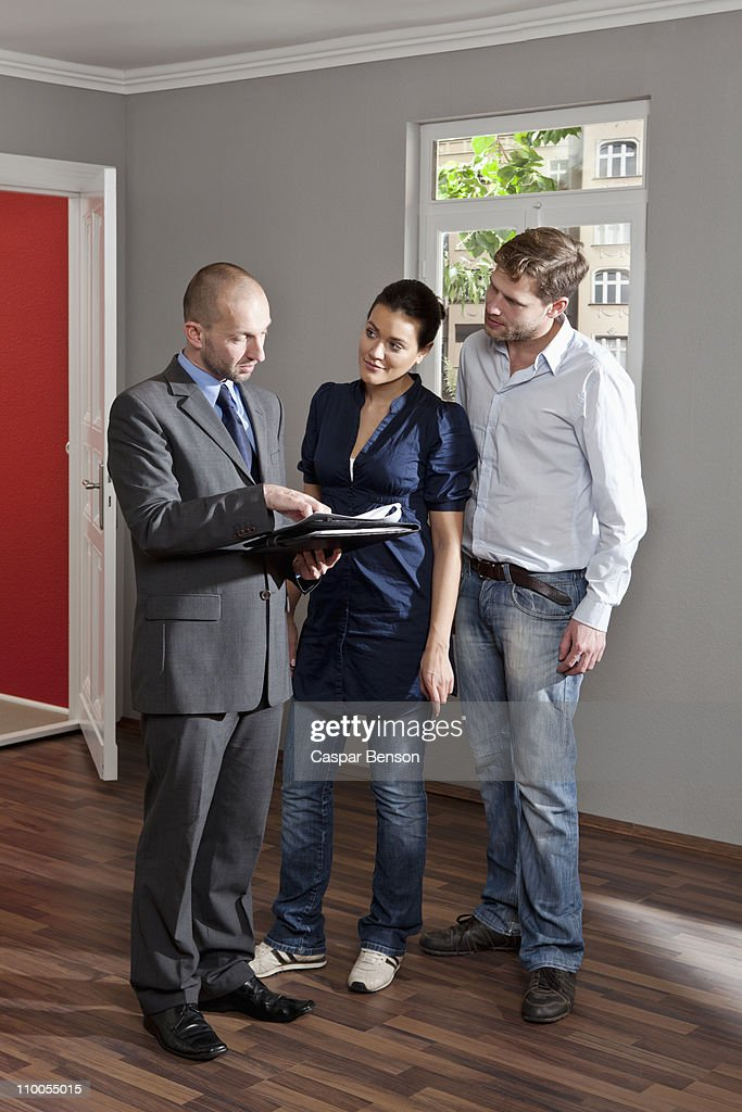 A real estate agent reviewing a contract with a couple