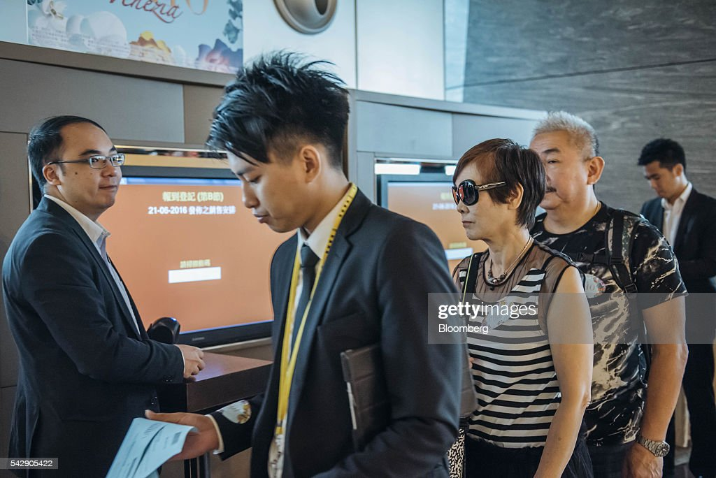 A real estate agent, second right, leads potential buyers into the sales office of Park Yoho Venezia, a residential property developed by Sun Hung Kai Properties Ltd., in Hong Kong, China, on Saturday, June 25, 2016. Sun Hung Kai, Hong Kong's largest developer by market value, is offering mortgages worth as much as 120 percent of a home's value at one of its projects as sales have slumped in the city. Photographer: Anthony Kwan/Bloomberg via Getty Images