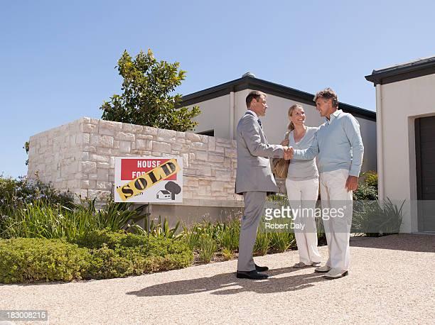agent immobilier, se serrant la main avec un couple à nouveau chez-vous