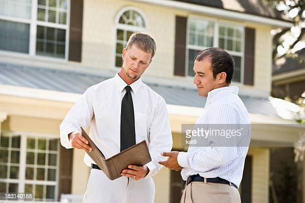 Real estate agent showing brochure in front of house