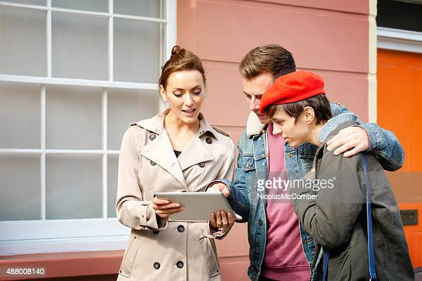 Real estate agent shows property details to couple using tablet