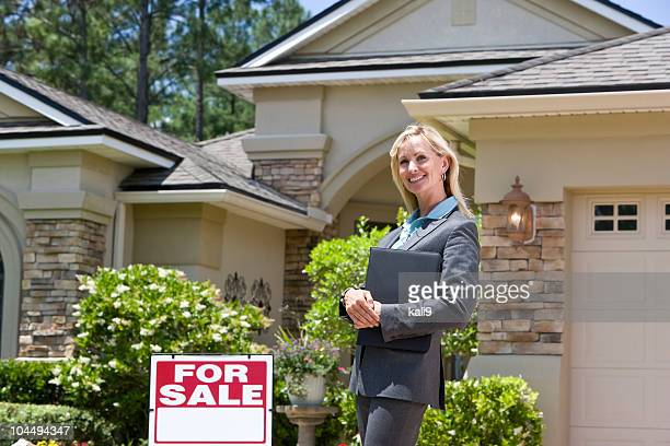 Real estate agent standing by For Sale sign outside house