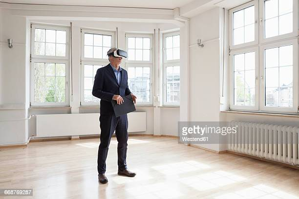 Real estate agent wearing virtual reality glasses in empty apartment