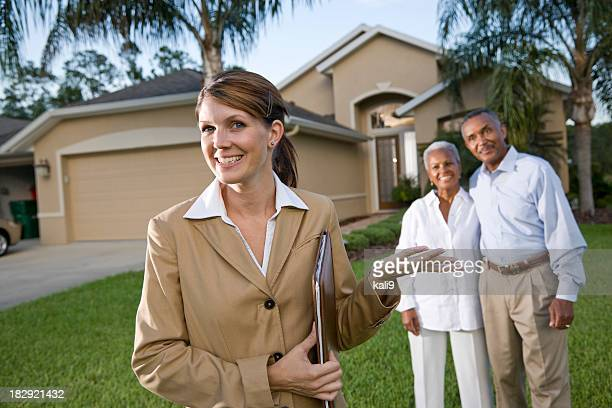 Real estate agent with African American couple outside house