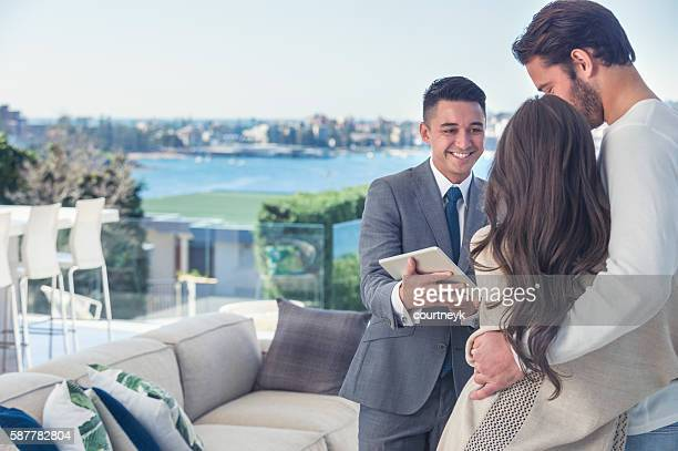 Real estate agent with couple in luxury home.