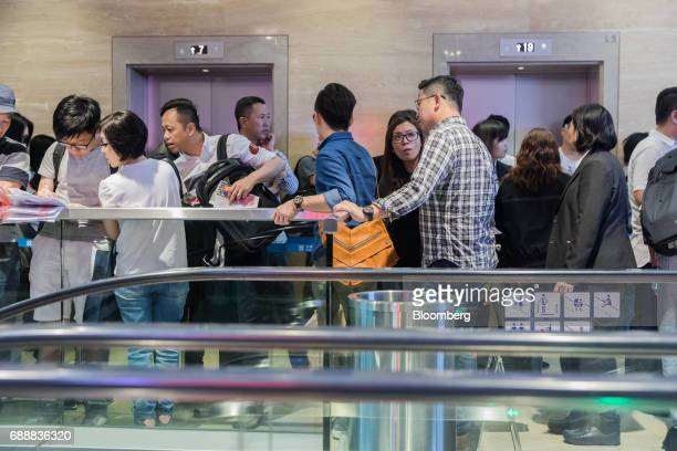 Real estate agents and potential buyers wait in line for an elevator to the sales office of the Victoria Skye residential development developed by KK...