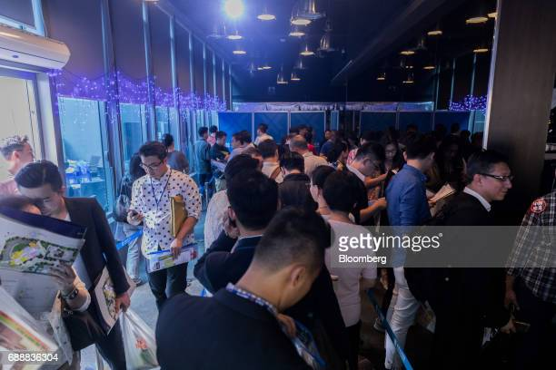 Real estate agents and potential buyers wait in line outside the sales office of the Victoria Skye residential development developed by KK Property...