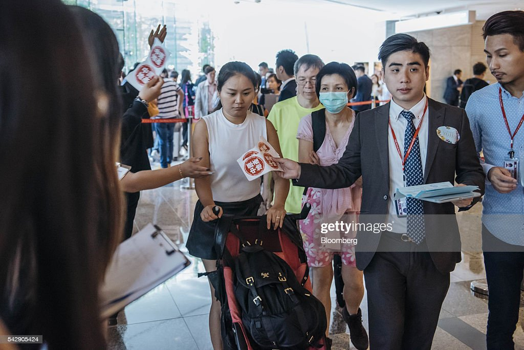Real estate agents, right and second right, lead potential buyers into the sales office of Park Yoho Venezia, a residential property developed by Sun Hung Kai Properties Ltd., in Hong Kong, China, on Saturday, June 25, 2016. Sun Hung Kai, Hong Kong's largest developer by market value, is offering mortgages worth as much as 120 percent of a home's value at one of its projects as sales have slumped in the city. Photographer: Anthony Kwan/Bloomberg via Getty Images