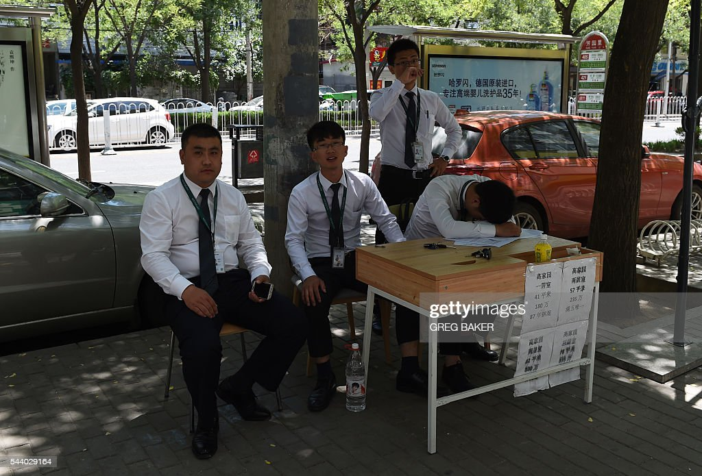Real estate agents sit on a sidewalk in Beijing on July 1, 2016. The cost of Chinese new homes rose at a slower rate in June from the previous month, figures showed on July 1, as measures to tame prices in the world's second-largest economy took hold. / AFP / GREG