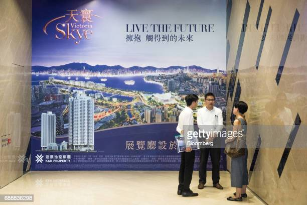 Real estate agents stand in front of an advertisement for the Victoria Skye residential development developed by KK Property Holdings Ltd outside the...