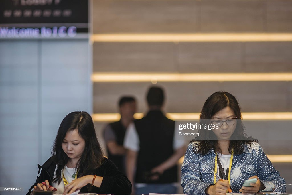 Real estate agents use smartphones at the sales office of Park Yoho Venezia, a residential property developed by Sun Hung Kai Properties Ltd., in Hong Kong, China, on Saturday, June 25, 2016. Sun Hung Kai, Hong Kong's largest developer by market value, is offering mortgages worth as much as 120 percent of a home's value at one of its projects as sales have slumped in the city. Photographer: Anthony Kwan/Bloomberg via Getty Images
