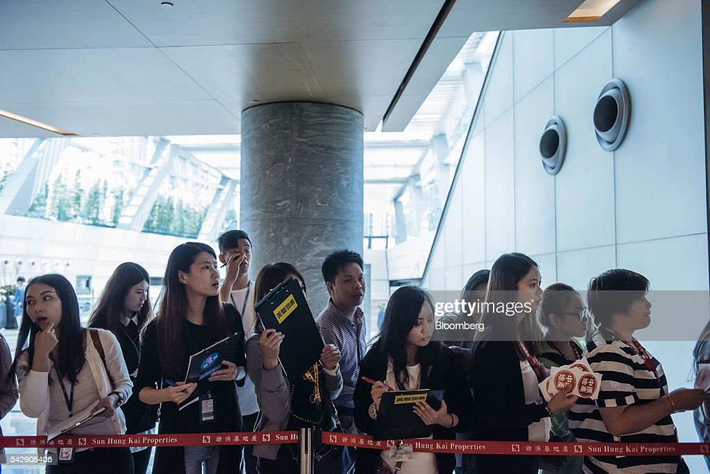 Real estate agents wait for potential buyers outside the sales office of Park Yoho Venezia, a residential property developed by Sun Hung Kai Properties Ltd., in Hong Kong, China, on Saturday, June 25, 2016. Sun Hung Kai, Hong Kong's largest developer by market value, is offering mortgages worth as much as 120 percent of a home's value at one of its projects as sales have slumped in the city. Photographer: Anthony Kwan/Bloomberg via Getty Images