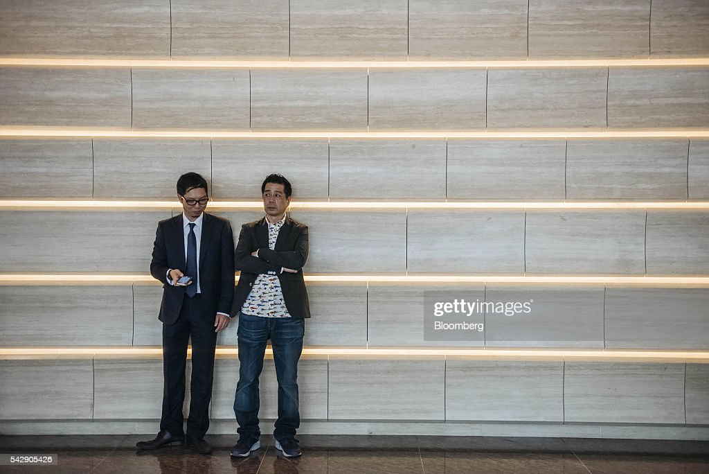 Real estate agents wait outside the sales office of Park Yoho Venezia, a residential property developed by Sun Hung Kai Properties Ltd., in Hong Kong, China, on Saturday, June 25, 2016. Sun Hung Kai, Hong Kong's largest developer by market value, is offering mortgages worth as much as 120 percent of a home's value at one of its projects as sales have slumped in the city. Photographer: Anthony Kwan/Bloomberg via Getty Images
