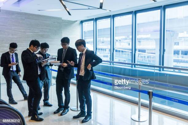Real estate agents wait outside the sales office of the Victoria Skye residential development developed by KK Property Holdings Ltd in Hong Kong...