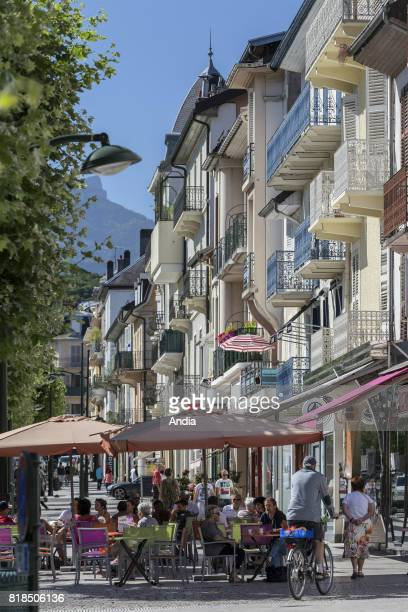 Real estate buildings and houses in downtown AixlesBains buildings and cafe terraces in the street 'rue de Geneve'