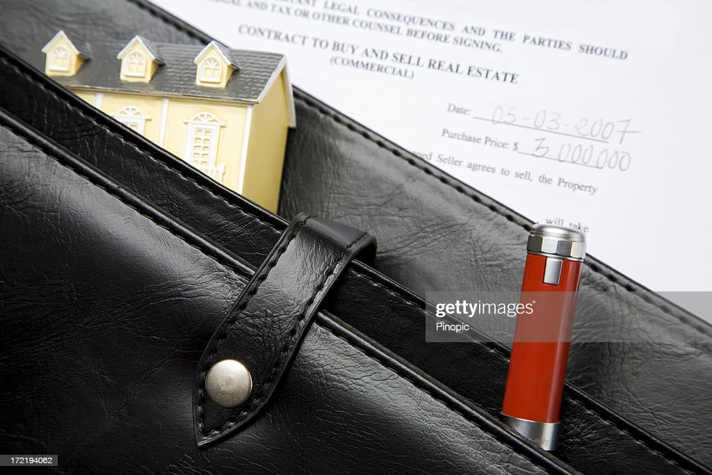 'Real Estate contract, toy house, pen  and briefcase'
