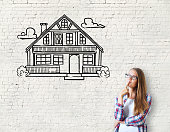 Attractive caucasian girl on brick background with house sketch. Real estate, mortgage and housing concept
