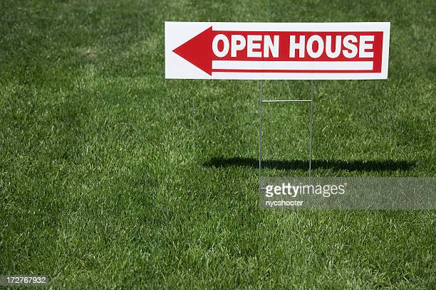 Real estate open house sign, red and white sign in grass.
