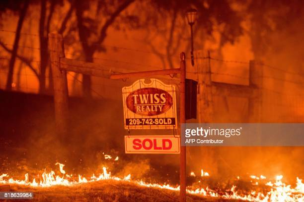 TOPSHOT A real estate sign is surrounded by flames as the Detwiler fire rages on near the town of Mariposa California on July 18 2017 California has...