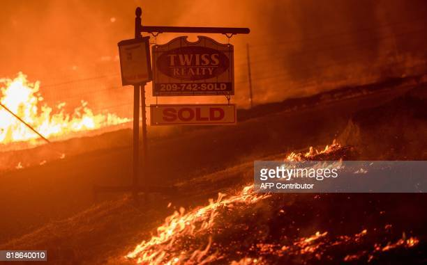 A real estate sign is surrounded by flames as the Detwiler fire rages on near the town of Mariposa California on July 18 2017 California has suffered...