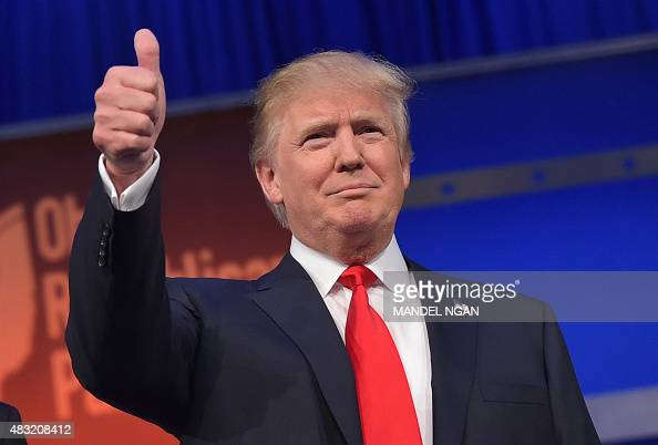 Real estate tycoon Donald Trump flashes the thumbsup as he arrives on stage for the start of the prime time Republican presidential debate on August...