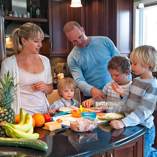 Real family of five making healthy lunch in kitchen.