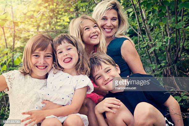 Real family of four kids posing with mother in summer.