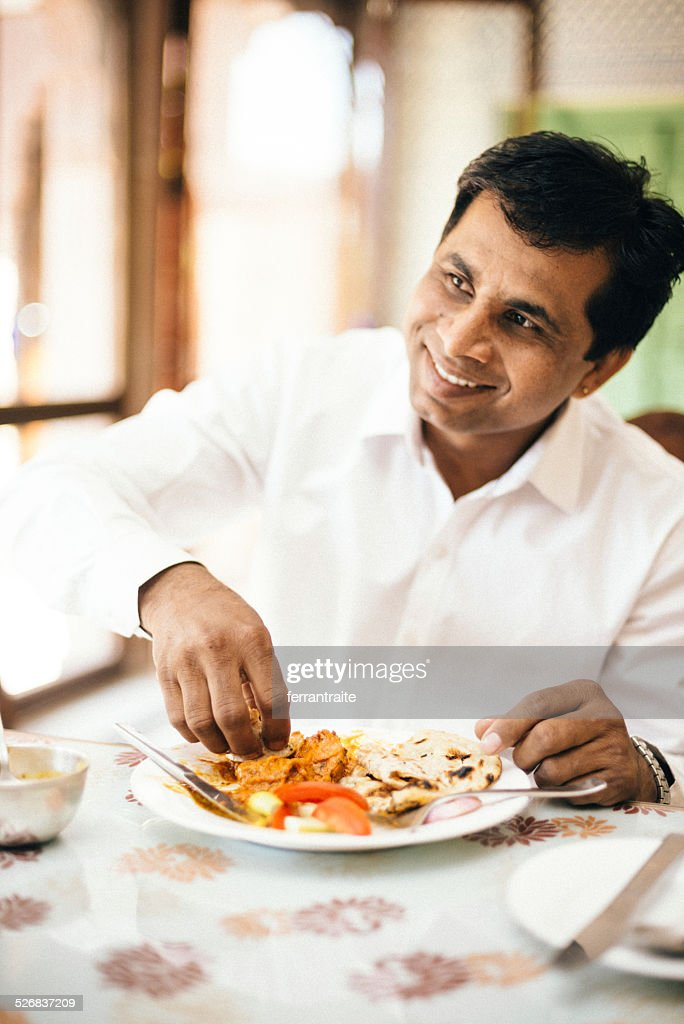 Real indian man eating with hands in indian restaurant for Cuisine you eat with your hands