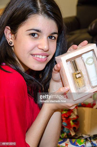 Real life Christmas scenes Girl holding boxed perfume bottle A girl with short dark hair and a red shirt shows the camera a pink box containing a...