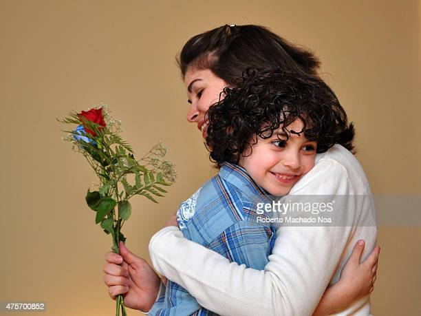 Real life Mother's day scene Little boy hugging mom with beautiful flower rose congratulates birthday