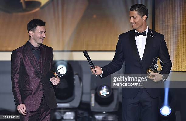 Real Madrid and Portugal forward Cristiano Ronaldo hands a microhpone to Barcelona and Argentina forward Lionel Messi as they stand on stage after...