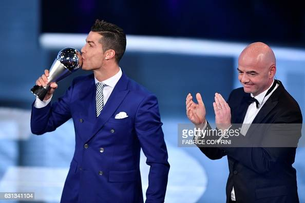 TOPSHOT Real Madrid and Portugal's forward Cristiano Ronaldo kisses his trophy after winning the The Best FIFA Mens Player of 2016 Award next to FIFA...