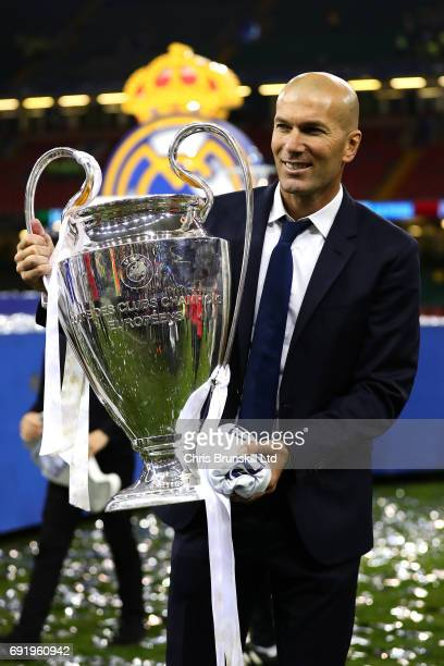 Real Madrid coach Zinedine Zidane poses with the trophy following the UEFA Champions League Final match between Juventus and Real Madrid at the...