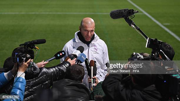 Real Madrid coach Zinedine Zidane talks in the mixed zone before a training session at Mitsuzawa Football Stadium on December 12 2016 in Yokohama...